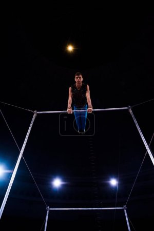 Photo for Low angle view of strong gymnast performing on horizontal bars in arena of circus - Royalty Free Image