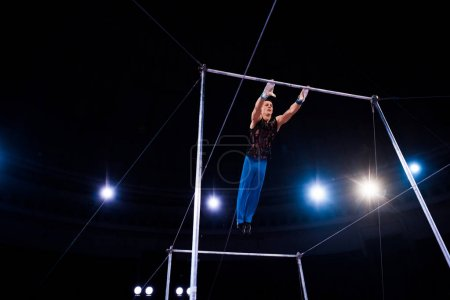 Photo pour Flexible gymnast performing on horizontal bars in arena of circus - image libre de droit