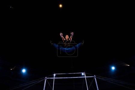 Photo pour Vue à faible angle du gymnaste sautant près des barres horizontales tout en exécutant dans le cirque - image libre de droit
