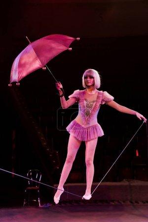 Photo pour Acrobate attrayant en costume tenant parapluie et debout sur la corde - image libre de droit