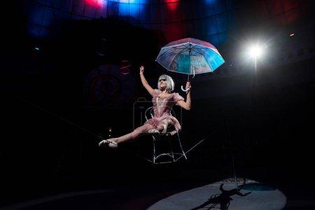 Photo pour Acrobate aérien tenant parapluie et équilibrage sur la corde tout en étant assis sur la chaise - image libre de droit