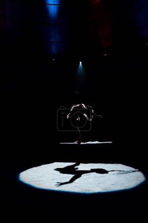Photo pour Silhouette d'acrobate aérien se produisant sur corde au cirque - image libre de droit