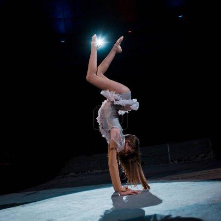 Photo pour Fille en costume faire handstand tout en effectuant dans l'arène de cirque - image libre de droit