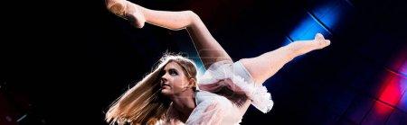Photo pour Plan panoramique de fille flexible en costume se produisant dans l'arène du cirque - image libre de droit