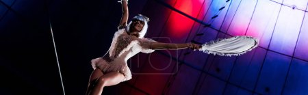 panoramic shot of attractive aerial acrobat holding racket while standing on rope