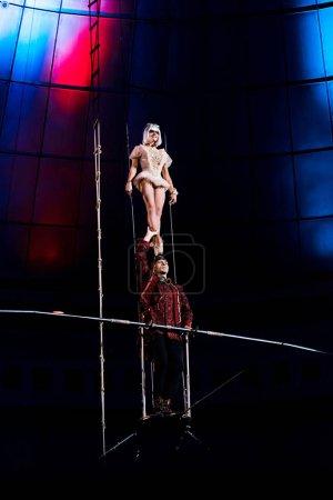 Photo pour Gymnaste soutenant acrobate attrayant tout en tenant la pole - image libre de droit