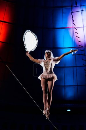 Photo for Aerial acrobat holding racket while balancing on rope - Royalty Free Image