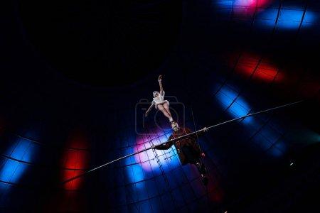 Photo pour Vue à faible angle de gymnaste beau soutenant acrobate attrayant tout en tenant le poteau - image libre de droit