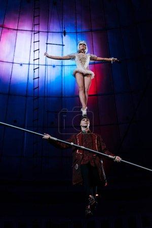 Photo pour Bel homme soutenant acrobate attrayant tout en tenant le poteau - image libre de droit