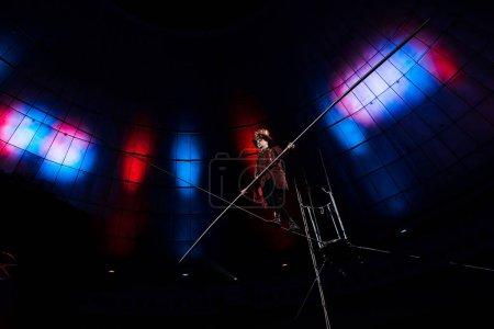 Photo pour Vue à faible angle du beau acrobate tenant le poteau et marchant sur la corde - image libre de droit