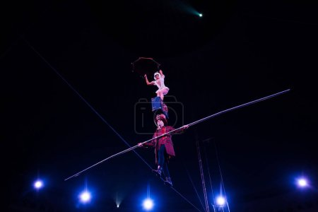 Photo for Low angle view of man holding pole and supporting attractive acrobat while walking on rope - Royalty Free Image