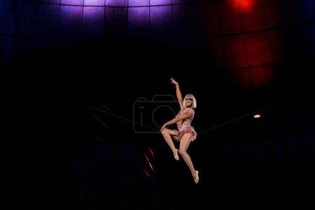 Photo pour Acrobate aérien artistique et heureux se produisant dans le cirque - image libre de droit