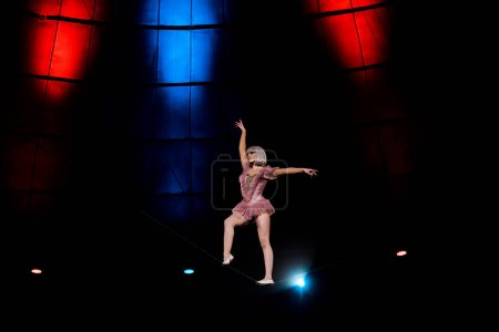 Photo pour Acrobate aérien artistique debout sur une corde se produisant dans un cirque - image libre de droit