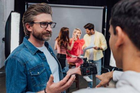 Photo pour Foyer sélectif du directeur artistique barbu dans les lunettes regardant assistant pointant du doigt à l'appareil photo numérique - image libre de droit