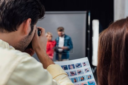 Photo for Back view of photographer taking photo of model and art director in photo studio - Royalty Free Image