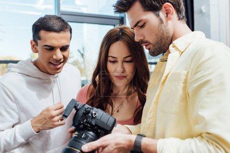 Photo pour Attrayant directeur artistique regardant appareil photo numérique près photographe et assistant - image libre de droit