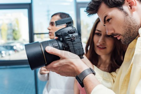 selective focus of attractive art director looking at digital camera near photographer
