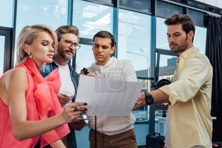 attractive model and handsome art director looking at photo collage with photographer and assistant