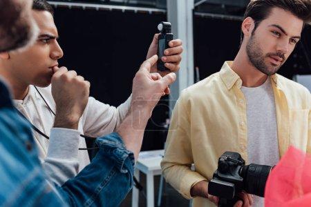 selective focus of man holding light meter near photographer