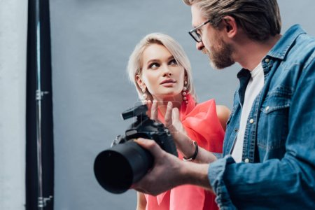 Photo for Selective focus of handsome art director holding digital camera and looking at beautiful model - Royalty Free Image
