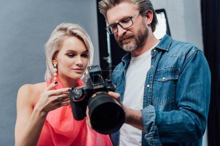 Photo pour Beau directeur artistique tenant appareil photo numérique près du modèle attrayant - image libre de droit