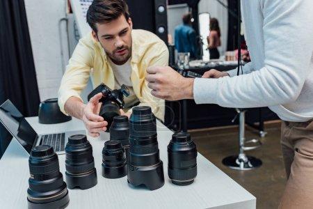 Photo pour Vue recadrée du directeur artistique debout près du photographe et des lentilles photo - image libre de droit