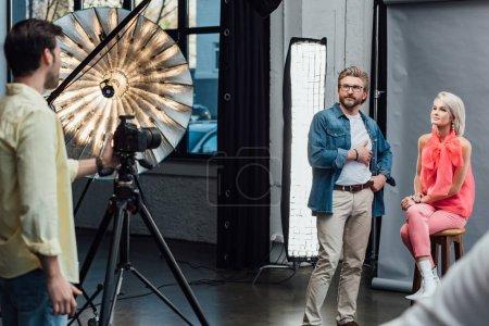 Photo pour Foyer sélectif de beau directeur artistique debout avec la main dans la poche près du modèle attrayant et en regardant photographe - image libre de droit