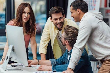 Photo pour Beau directeur artistique en lunettes regardant des assistants heureux - image libre de droit