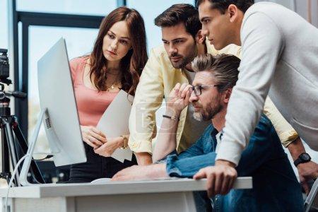 Photo pour Directeur créatif barbu touchant des lunettes et regardant l'écran d'ordinateur avec des collègues - image libre de droit