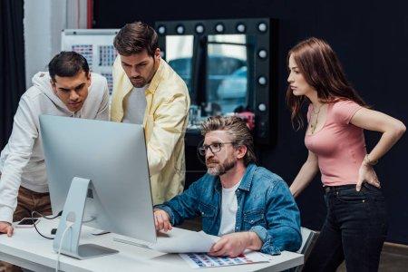 Photo pour Directeur créatif dans les lunettes regardant moniteur d'ordinateur avec des collègues - image libre de droit