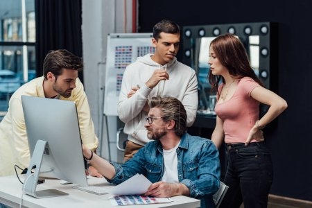 creative director in glasses looking at assistant near computer monitor