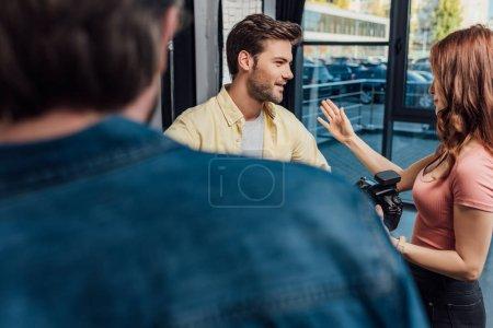 Photo pour Foyer sélectif de photographie attrayant geste tout en regardant l'homme près du directeur artistique - image libre de droit