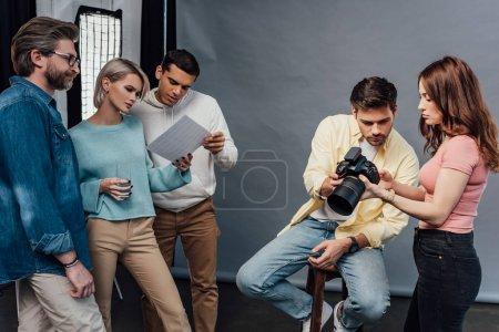 Photo pour Photographe tenant appareil photo numérique près de beau modèle et collègues - image libre de droit