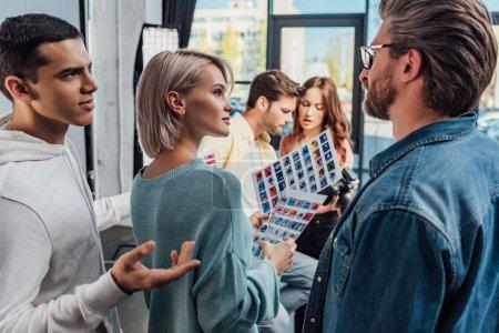 enfoque selectivo del director de arte mirando gestos de asistente en el estudio de fotografía