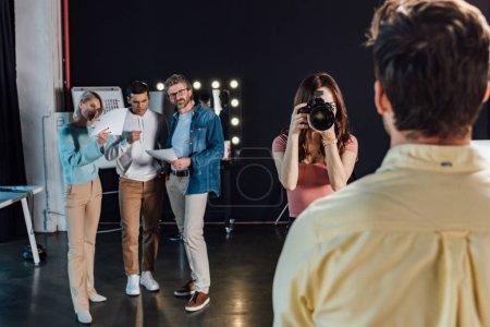 Photo pour Foyer sélectif du photographe prenant une photo de l'homme près du directeur artistique et des collègues - image libre de droit