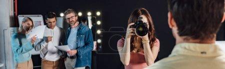 Photo pour Prise de vue panoramique d'un photographe photographiant un homme près du directeur artistique et de ses collègues - image libre de droit