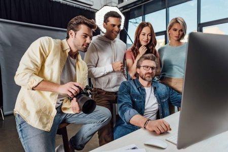 Photo pour Foyer sélectif du directeur créatif heureux et des assistants regardant le moniteur d'ordinateur dans le studio de photo - image libre de droit