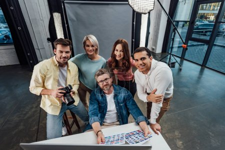 overhead view of happy creative director and assistants looking at camera in photo studio