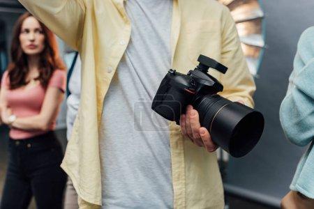 Photo pour Foyer sélectif du photographe tenant un appareil photo numérique - image libre de droit