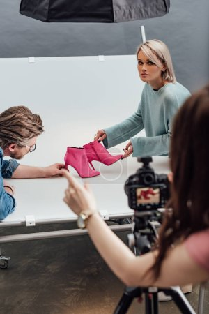 cropped view of photographer pointing with finger near attractive assistant and art director holding pink shoes