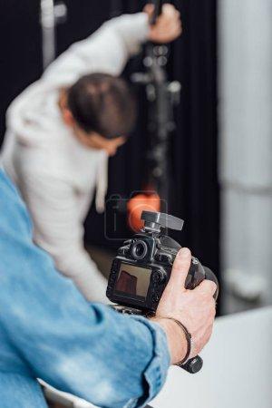 Photo pour Foyer sélectif de l'appareil photo numérique moderne sur trépied près du photographe - image libre de droit