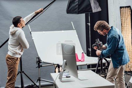 Photo pour Beau assistant toucher réflecteur tandis que photographe photo tir chaussures - image libre de droit