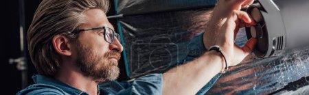 Photo pour Prise de vue panoramique du directeur artistique barbu touchant réflecteur dans le studio photo - image libre de droit