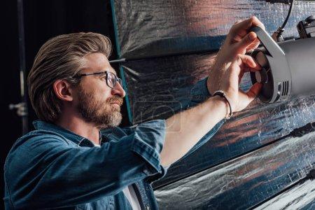 Photo pour Directeur artistique barbu touchant réflecteur dans le studio photo - image libre de droit