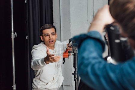Photo pour Focus sélectif de belles gesticulations d'assistant en parlant près de l'homme en studio de photographie - image libre de droit