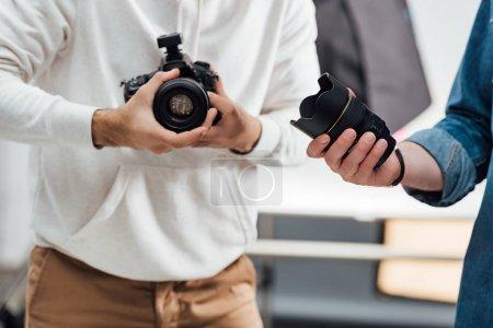 Photo pour Crochet d'un photographe tenant un appareil photo numérique près du directeur artistique avec lentille de l'appareil - image libre de droit