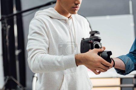 Photo pour Vue recadrée du photographe tenant un appareil photo numérique et prenant l'objectif de l'appareil photo - image libre de droit