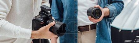 Photo pour Photo panoramique d'un directeur artistique tenant un objectif près du photographe - image libre de droit