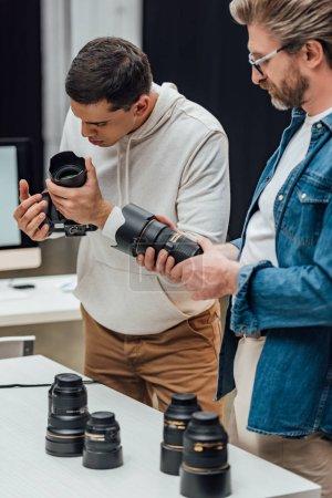 Photo pour Bearded art director tenant une lentille photo près du photographe - image libre de droit