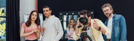 Photo pour Photo panoramique d'un photographe prenant une photo près du directeur artistique en lunettes et montrant le pouce vers le haut - image libre de droit